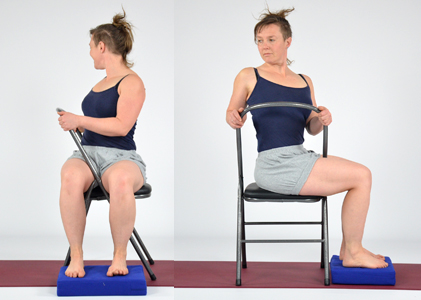 Person demonstrating yoga twist on chair. Sitting sideways twisting to rear of chair